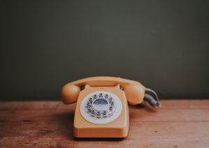 Vieux téléphone orange sur une table en bois