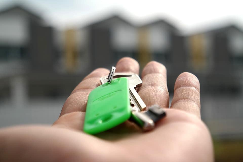 Agent immobilier qui tient les clés d'une maison dans sa main