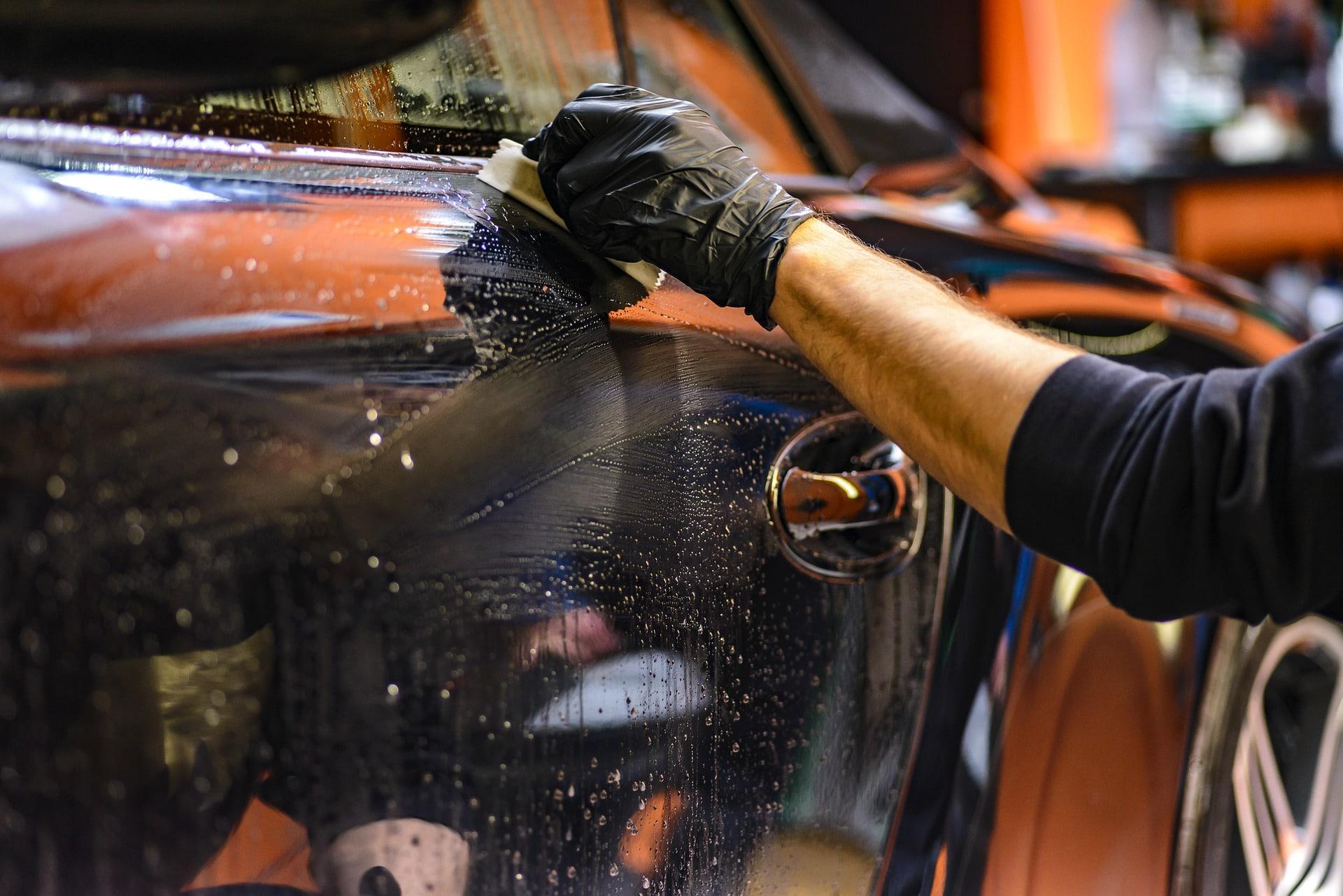 Homme qui nettoie une voiture avec une éponge