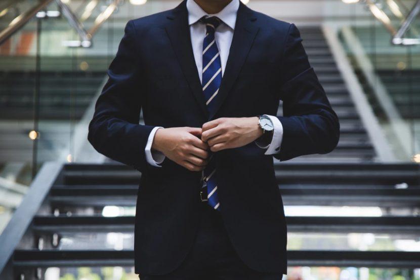 Cadre dirigeant en costume cravate dans les escaliers de son entreprise