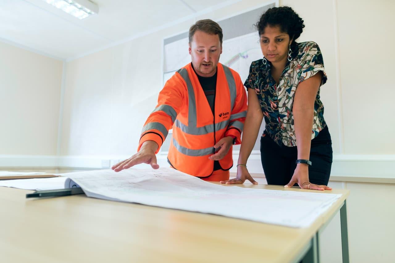 un ouvrier et sa supérieure qui examinent un plan