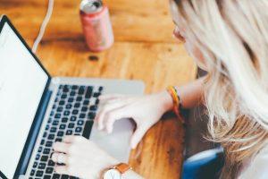 femme sur un pc posé sur un bureau avec une canette à côté